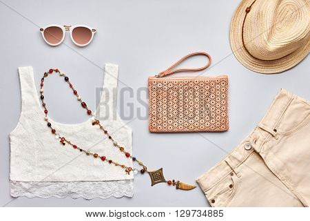 Summer Fashion girl clothes set, accessories. Creative urban hipster pastel colors. Stylish lace top, trendy sunglasses, handbag clutch, necklace, beige hat. Unusual modern.Overhead, top view on gray