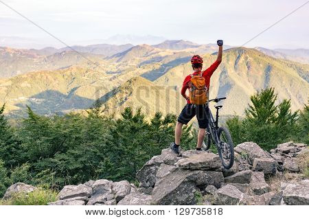 Mountain biker success looking at view on bike trail in autumn mountains. Successful happy rider on rocks. Sport adventure motivation and inspiration.