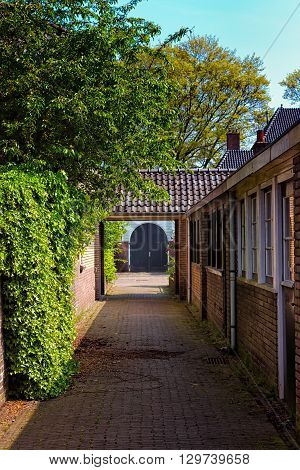 A blue double door at the end of a narrow corridor in a pittoresque residental area in the town of Bussum the Netherlands.