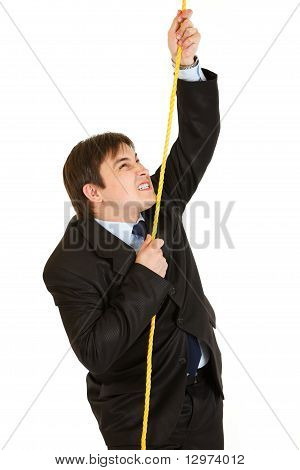 Stubborn businessman climbing up on rope isolated on white