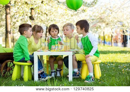 Happy sweet preschool children friends and relatives celebrating fifth birthday of cute boy outdoor in blooming apple tree garden springtime late afternoon