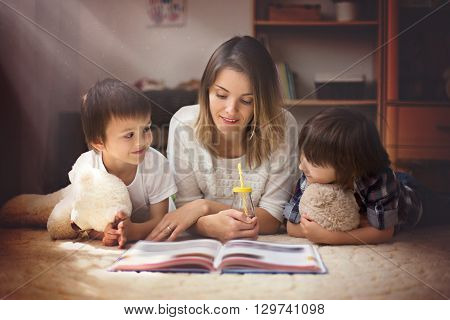 Young mother read a book to her tho children boys in the living room