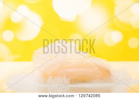 The bathroom soap with foam on an abstract yellow background