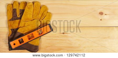 Level And Gloves Wrench On Wooden Background