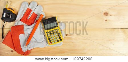 Calculator, Pencil And Gloves Wrench On Wooden Background