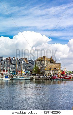 Honfleur France - May 19 2012: Normandy traditional houses and boats in the old harbor basin