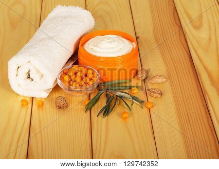 Towel, sea buckthorn and cream out of it against the backdrop of pale wood