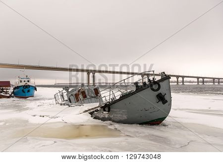 Boat wreck in a frozen river covered with ice