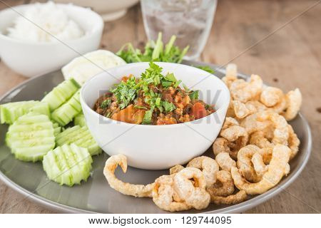 Nam Prik Ong chili pork Fried pork skin Vegetable on wooden floor.Thai style cuisine.