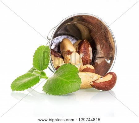 bucket and roasted hazel nuts spill out of him, isolated on white background