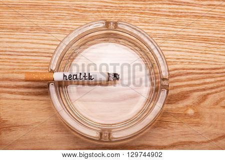Charred cigarette Hilton inscription in an ashtray on a background of light wood
