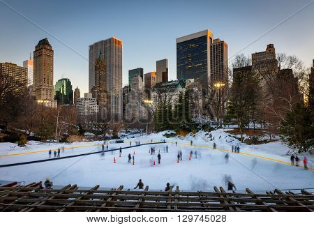 Winter scene in Central Park: the Wollman Rink at sunset with Manhattan Midtown skyscrapers. New York City