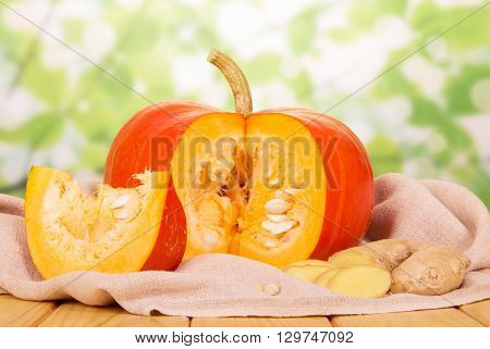 Mature pumpkin and cut pieces of ginger on an abstract green background.