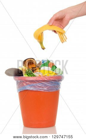 The female hand puts a banana peel in a bucket of household waste isolated on white background.