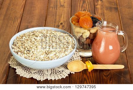 Bowl with oat flakes, a jug of juice, nuts and dried fruits on a background of dark wood.
