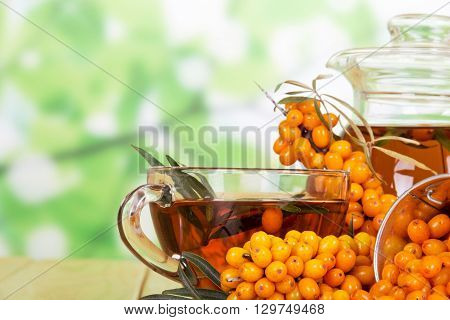 Bunches of sea buckthorn, a jug and a cup with a drink from her abstract green background.
