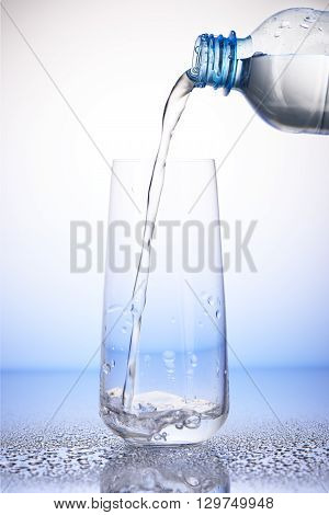 Water Pouring From Bottle Into Drinking Glass On Drops