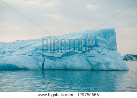 Big piece of iceberg in Iceland. Floating glacier in Jokulsarlon lagoon. Blue ice.