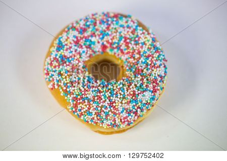 fresh doughnuts with sprinkles, on white ground