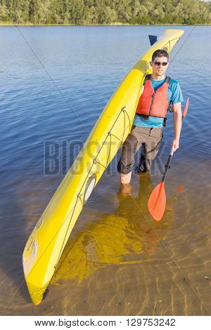 Man traveling on the river in a kayak in the summer.