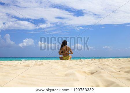 Woman meditating at the beach in a yoga retreat. Playa del Carmen, Mexico.