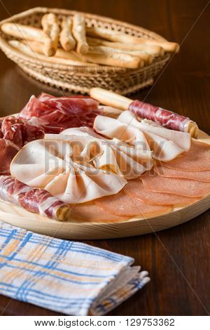 Salami chopping board with breadsticks on a wicker basket and napkin