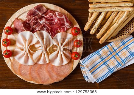 Salami cutting board breadsticks and napkin seen from above