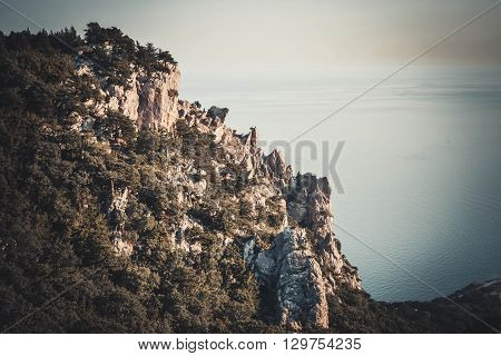 sharp tip of a cliff with trees and sea Crimea Southern Coast