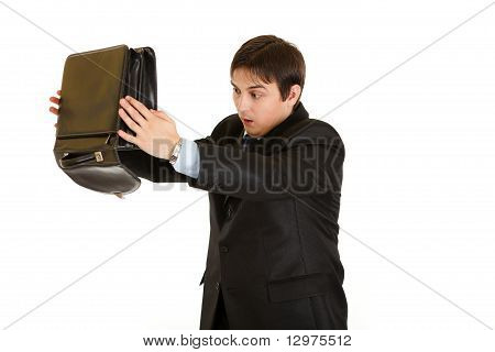 Shocked modern businessman searching something in briefcase isolated on white