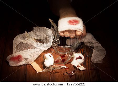 Bandaged wounded by a hand against the dark wood.