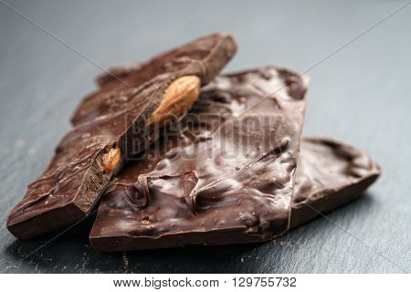 reverse side homemade chocolate with almond nuts on slate board, shallow focus