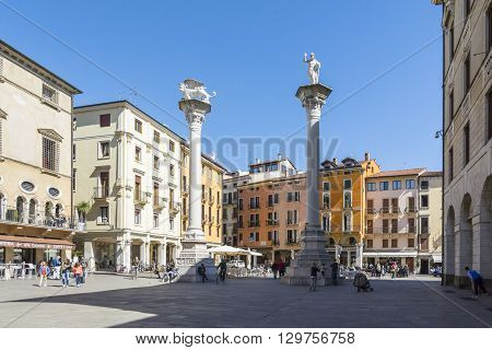 VICENZA,ITALY-APRIL 3,2015:people walk and admire the famous town square named Piazza dei Signor in Vicenza Italy during a sunny day.The tower was build by famous architect Andrea Palladio.