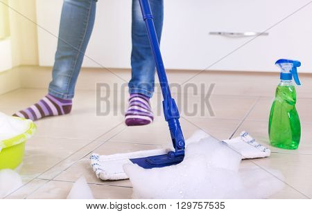 Close up of mop on kitchen tiles with soap foam woman in jeans and socks mopping floor