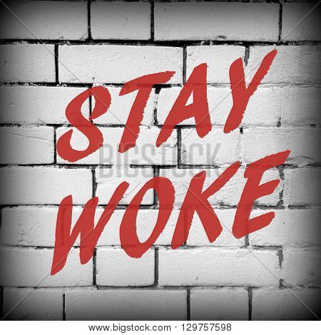 The words Stay Woke in red text on a white brick wall as a reminder to remain aware and stay informed about politics and other issues.