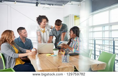 Group of young casual employees discussing a brainstorming project while researching ideas on a computer.