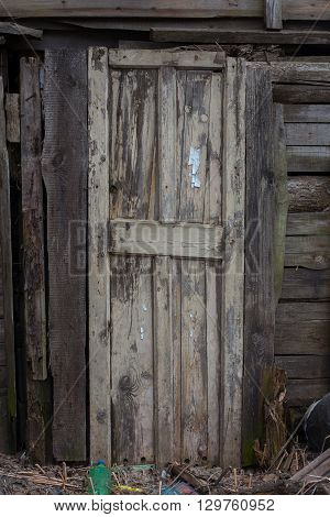 old shabby wooden door in destroyed house