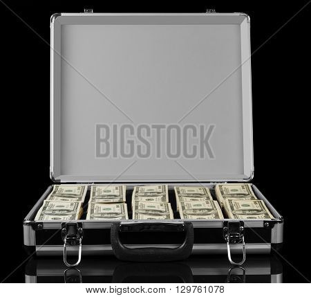 Opened suitcase with dollars isolated on a black background.