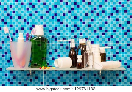 Shelf with toiletries and cosmetics on background bathroom.