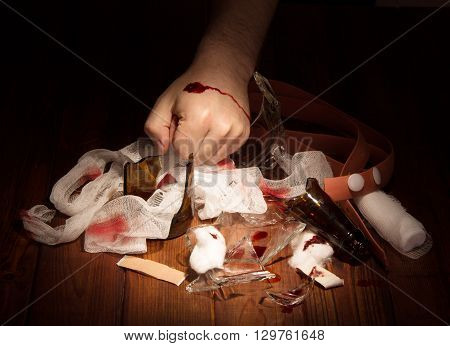Man's hand with a bleeding wound and debris against the dark wood.