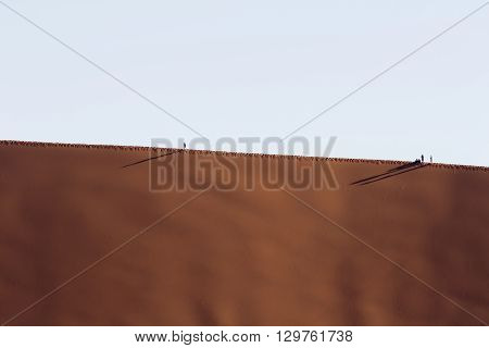 People walking on the crest of a red dune in the Namib Desert in Sossusvlei in the Namib-Naukluft National Park of Namibia
