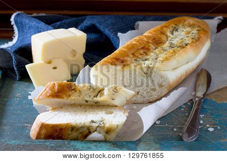 Bread Long Loaf Baguette With Cheese And Herbs On A Vintage Wooden Blue Background.