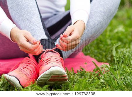 Woman Tying Sneakers On Grass