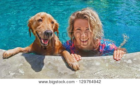 Funny portrait of smiling woman playing with dog and training golden retriever puppy in blue swimming pool. Popular dog breeds outdoor activity and fun games with family pet on summer beach holiday.