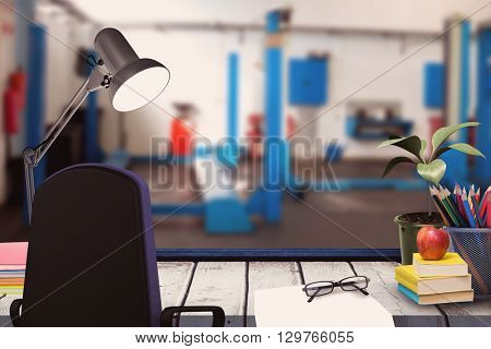 A desk with lamp and documents against empty work stations