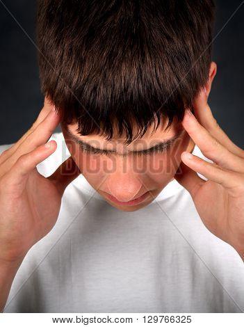 Young Man Feels Headache on the Dark Background
