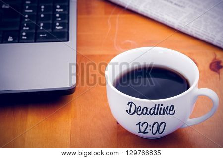 Deadline sentence against a cup of coffee with a laptop and a newspaper