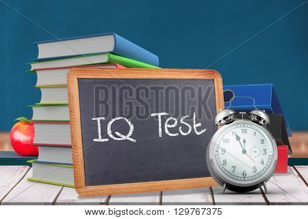Word IQ TEST against red apple on pile of books in classroom