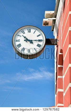 The City Of St. Petersburg.The clock hanging on the wall of the building and passers-by show time.