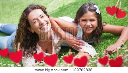 Composite image of mother and daughter lying on grass behind heart tinsel