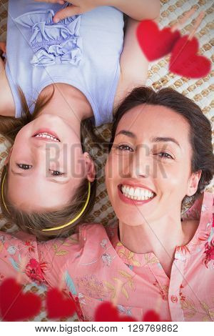 Hearts hanging on a line against mother and daughter smiling at camera